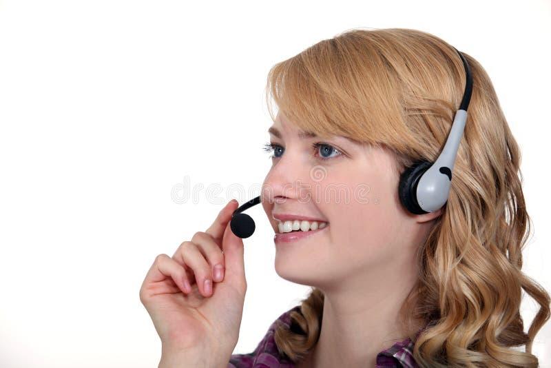Frau mit einem Telefonkopfhörer lizenzfreie stockfotografie