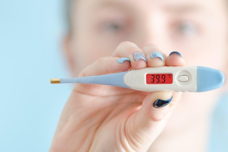 Frau mit einem Thermometer in seiner Hand Erhöhte Körpertemperatur lizenzfreie stockfotos