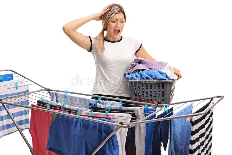 Frau mit einem Wäschekorb, der im Unglauben ihren Kopf hält stockfotografie