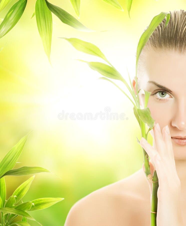 Frau mit einer Bambusanlage lizenzfreie stockfotos