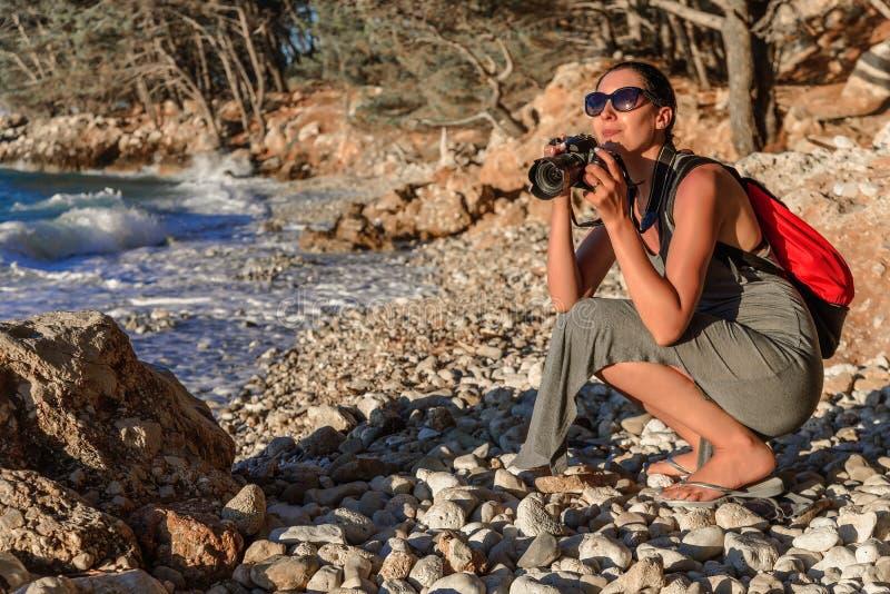 Frau mit einer Kamera den Sonnenuntergang auf der Seeküste fotografierend lizenzfreie stockfotografie