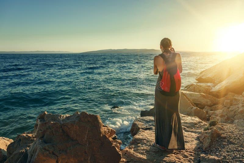 Frau mit einer Kamera den Sonnenuntergang auf der Seeküste fotografierend stockbilder