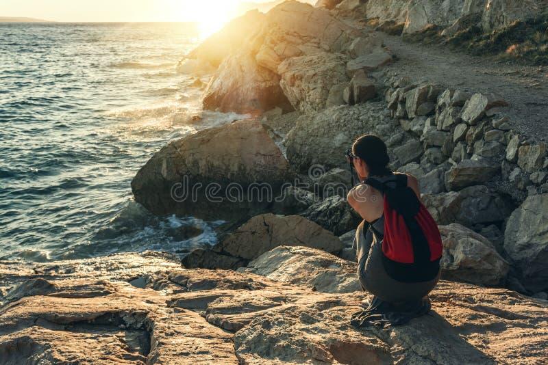Frau mit einer Kamera den Sonnenuntergang auf der Seeküste fotografierend stockfoto