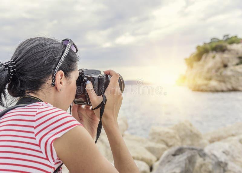 Frau mit einer Kamera den Sonnenuntergang auf der Seeküste fotografierend lizenzfreie stockbilder