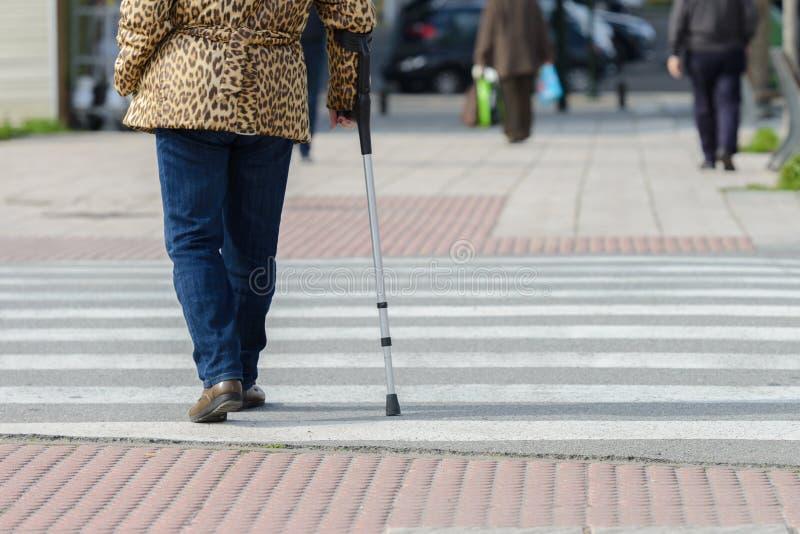 Frau mit einer Krücke an einem Fußgängerübergang, hintere Ansicht lizenzfreie stockfotografie