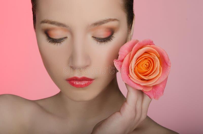 Frau mit einer Rose schloss ihre Augen lizenzfreie stockbilder