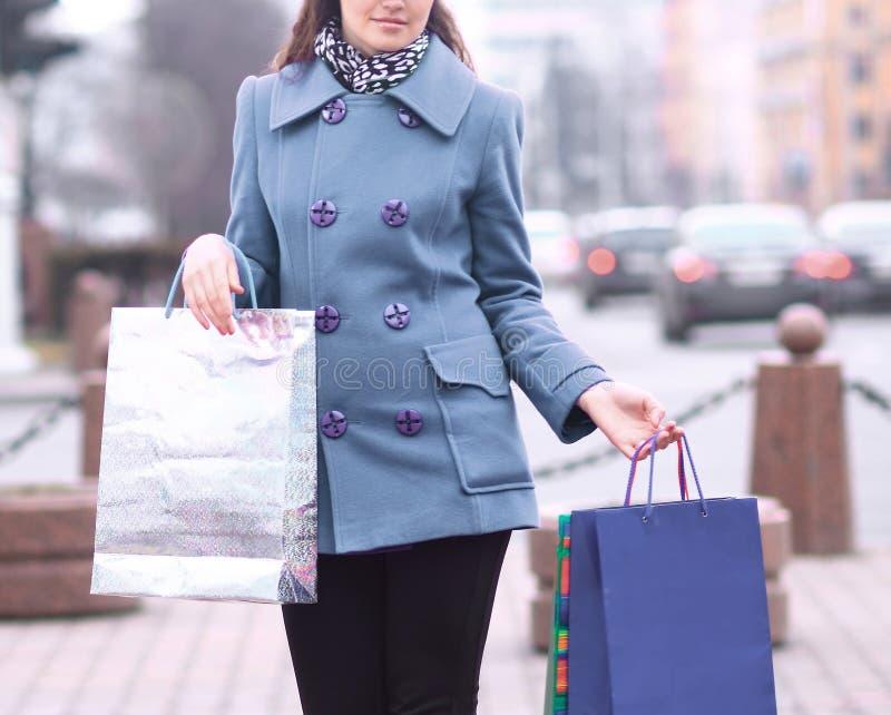 Frau mit Einkaufstaschen auf dem Hintergrund der Stadt stockbilder