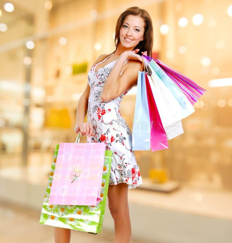 Frau mit Einkaufstaschen am Shop lizenzfreie stockbilder