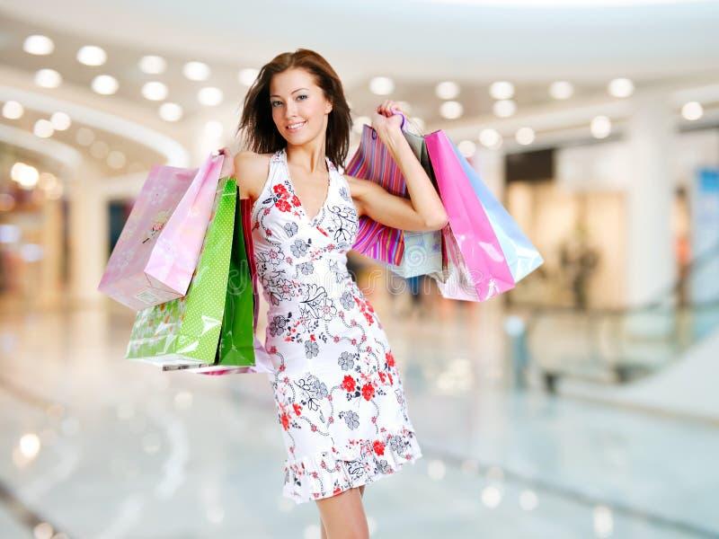 Frau mit Einkaufstaschen am Shop stockbild