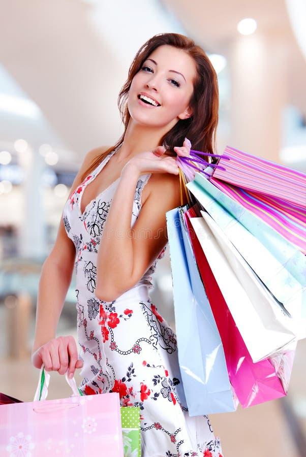 Frau mit Einkaufstaschen am Shop stockfotografie