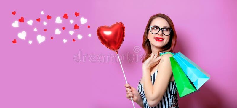 Frau mit Einkaufstaschen und Herzen stockfotos