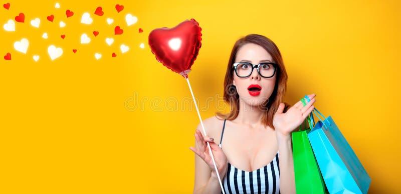 Frau mit Einkaufstaschen und Herzen lizenzfreie stockfotos
