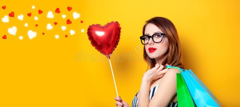 Frau mit Einkaufstaschen und Herzen lizenzfreie stockbilder