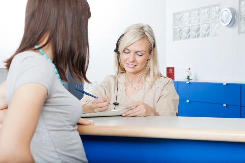 Frau mit Empfangsdamen-Filling Form At-Zahnarzt lizenzfreie stockbilder