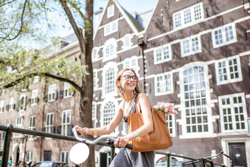 Frau mit Fahrrad in Amsterdam-Stadt lizenzfreies stockbild