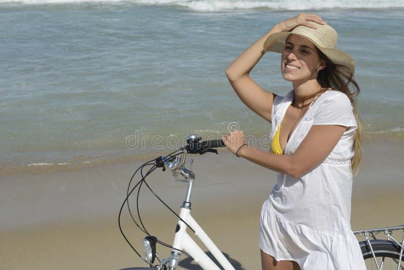 Frau mit Fahrrad auf dem Strand stockbild