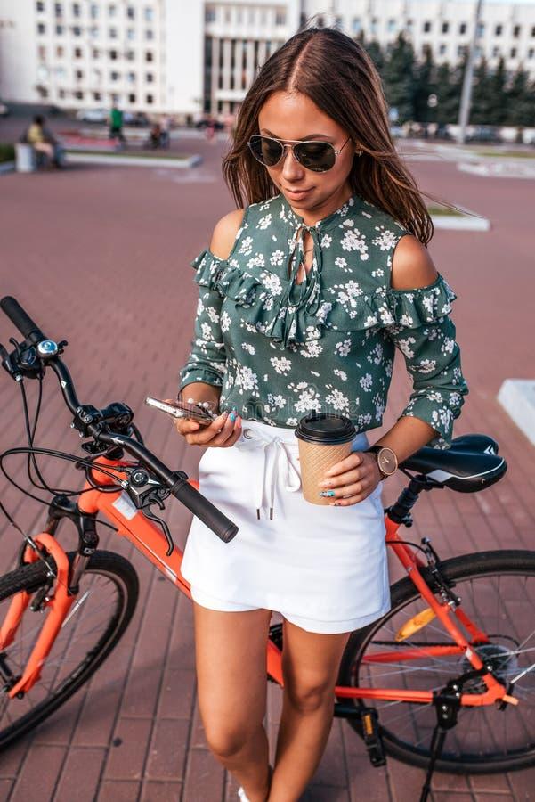 Frau mit Fahrrad, Sommerstadt Gr?ne Jacke und wei?e Rockkurze hosen Lange Haarsonnenbrille In seinem Handsmartphone stockfotografie