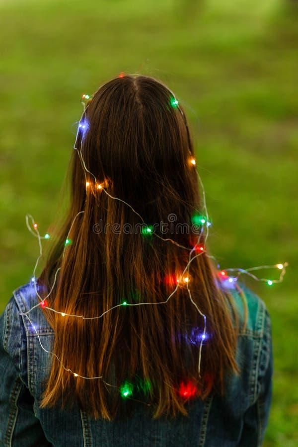 Frau mit feenhaften Lichtern der Girlande draußen nachts, Weinleseart Dunkles behaartes W?sche-Baumuster Hippie-Mädchentanzen in  stockbilder