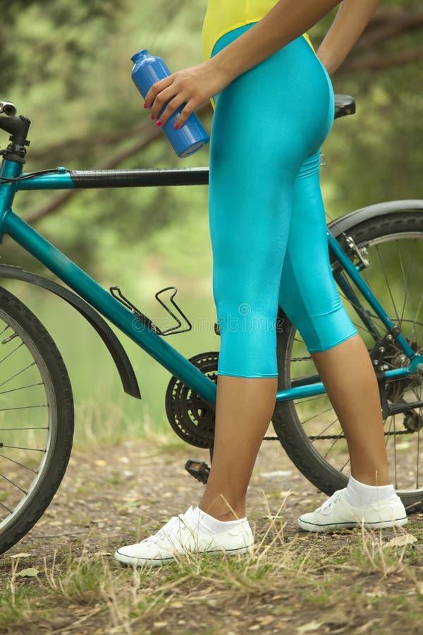 Frau mit Flasche und Fahrrad stockbilder