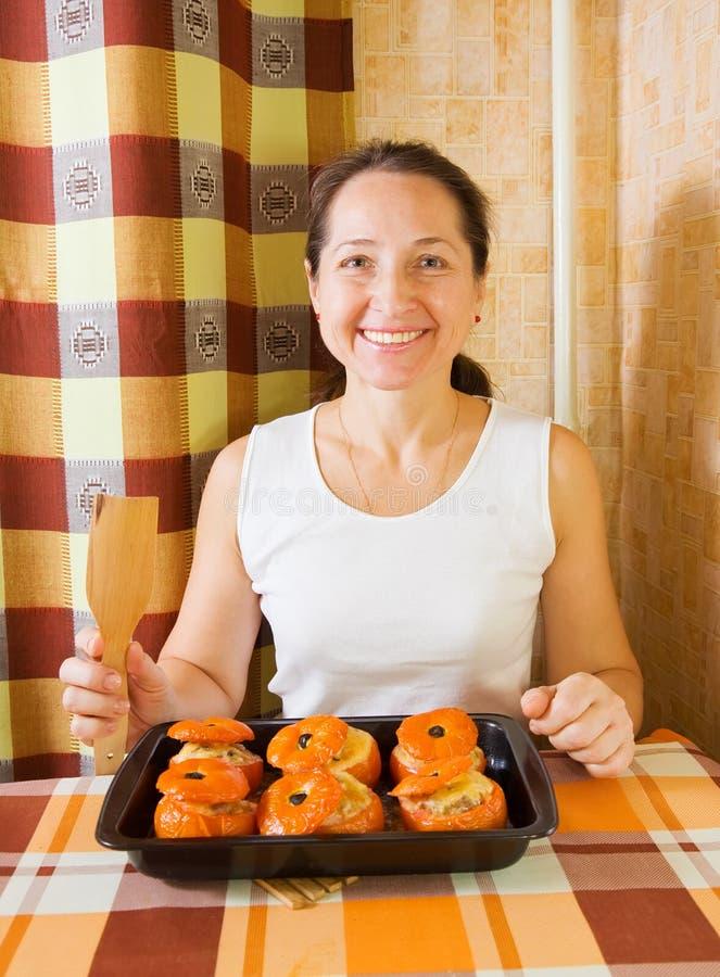 Frau mit gebratener farci Tomate stockfotos