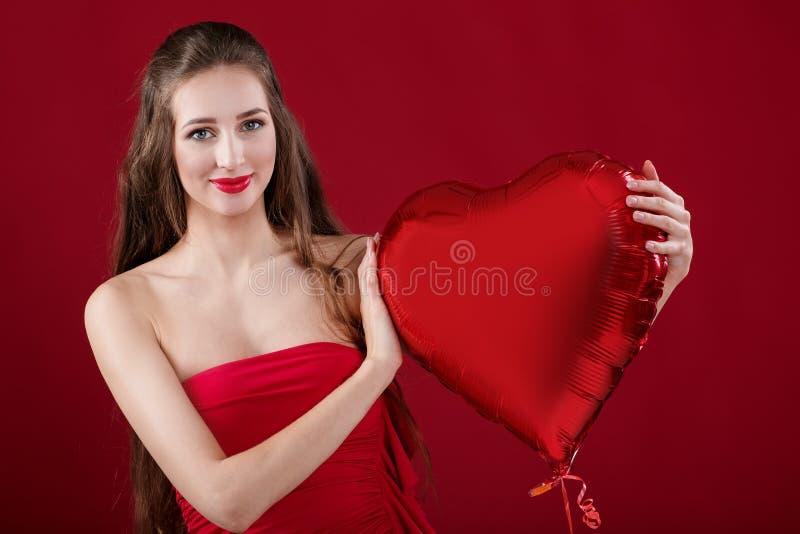 Frau mit geformten Luftballonen des Herzens stockbild