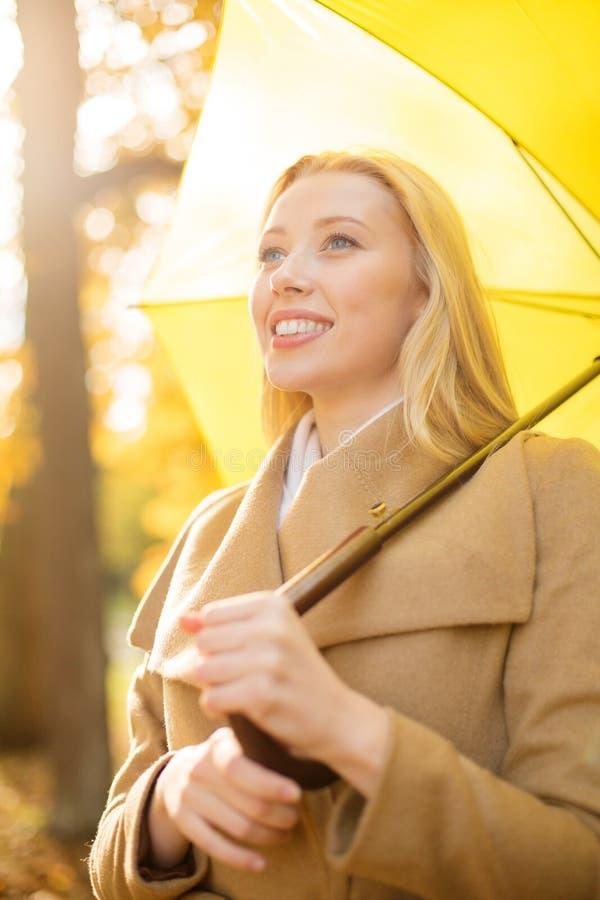 Frau mit gelbem Regenschirm im Herbstpark lizenzfreie stockbilder