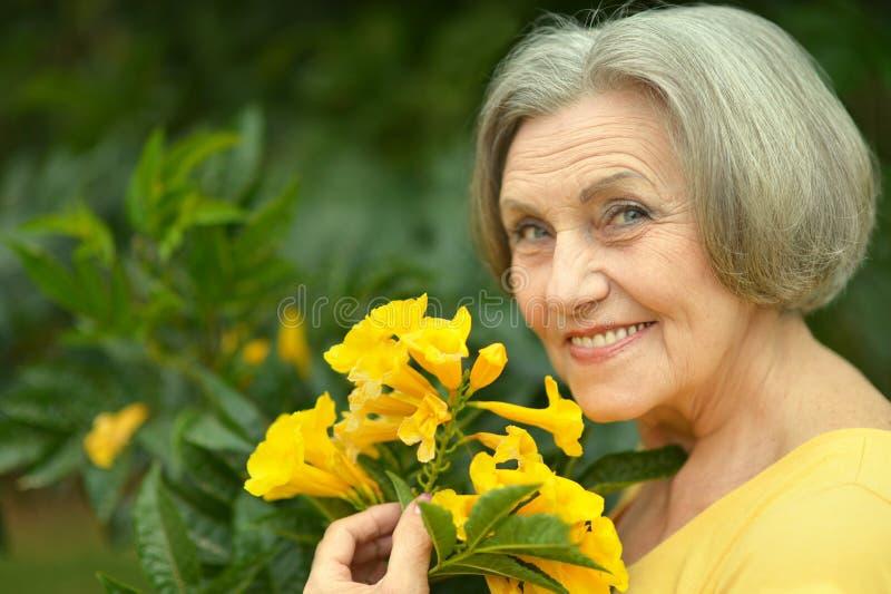 Frau mit gelben Blumen lizenzfreie stockbilder