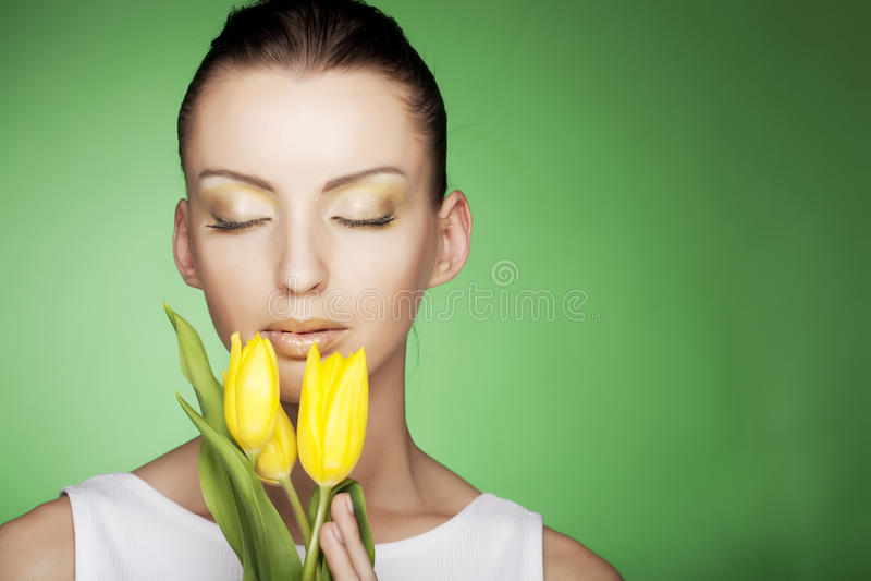 Frau mit gelben Blumen auf grünem Hintergrund stockbild