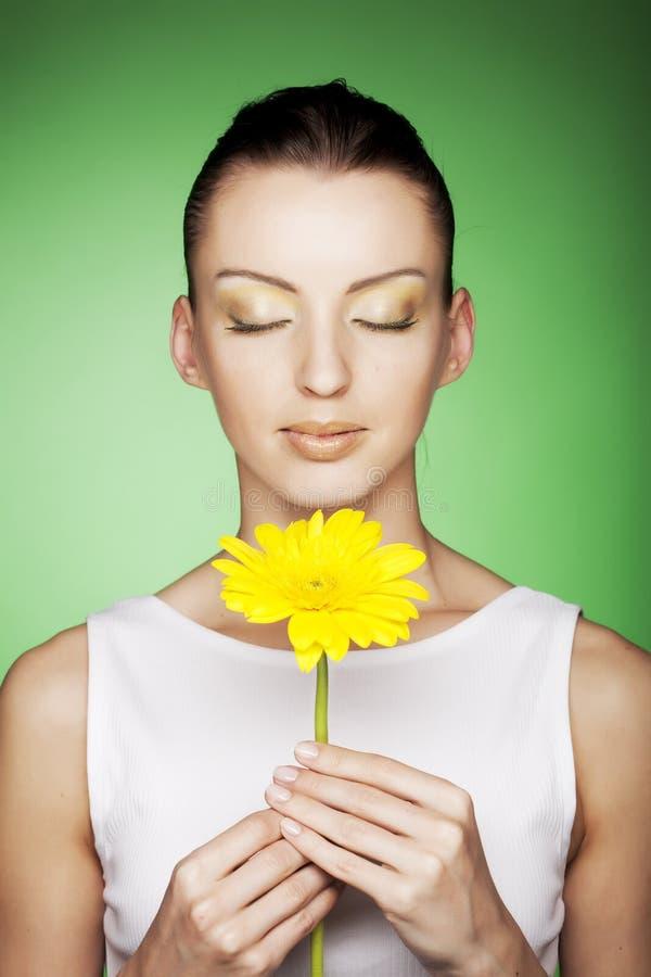 Frau mit gelben Blumen auf grünem Hintergrund lizenzfreie stockbilder