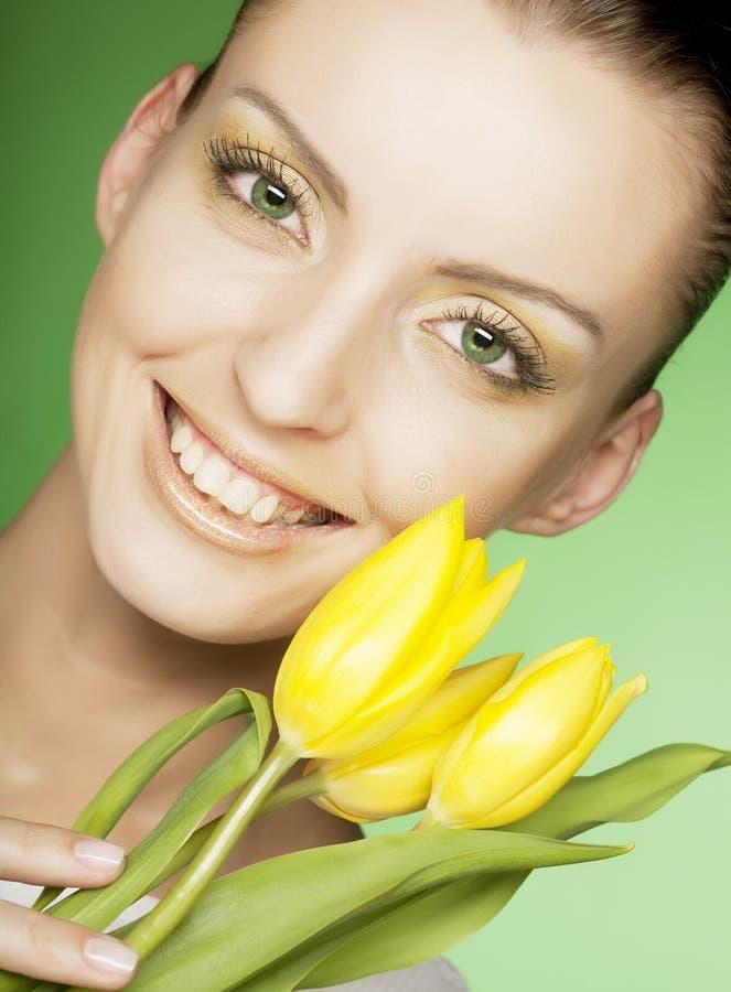 Frau mit gelben Blumen auf grünem Hintergrund stockfoto