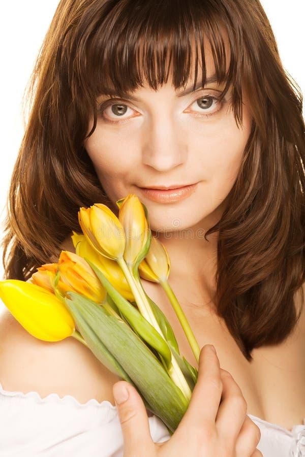 Frau mit gelben Tulpen stockbild