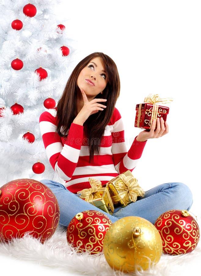 Frau mit Geschenk nahe bei weißem Weihnachtsbaum stockfoto