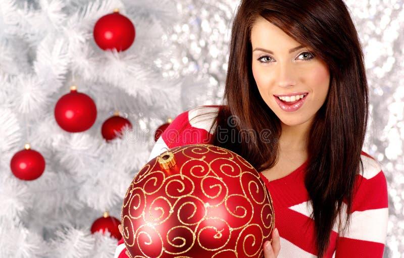 Frau mit Geschenk nahe bei weißem Weihnachtsbaum lizenzfreies stockbild