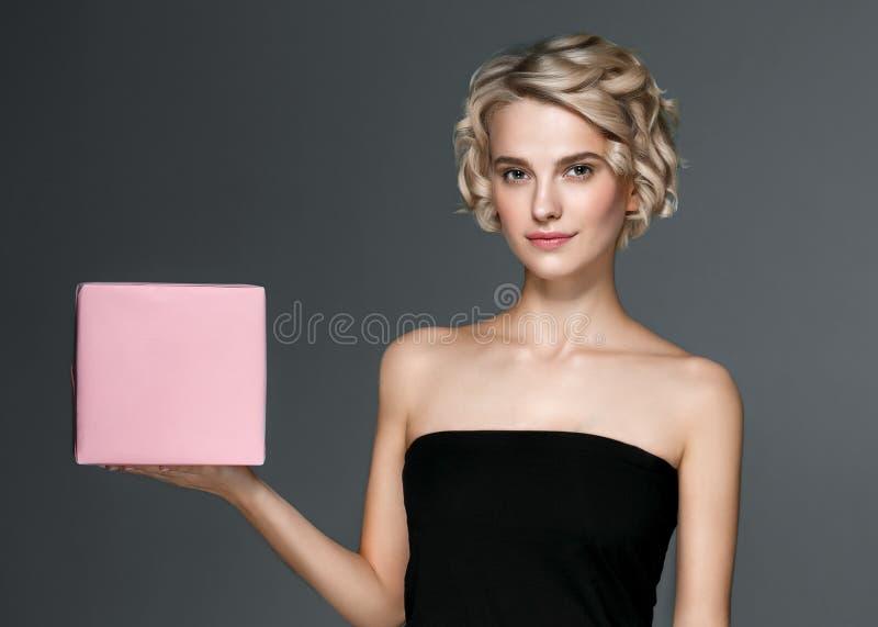Frau mit Geschenkbox überreicht herein grauen Hintergrund lizenzfreie stockbilder