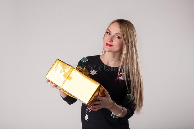 Frau mit Geschenkbox im goldenen Packpapier stockbilder