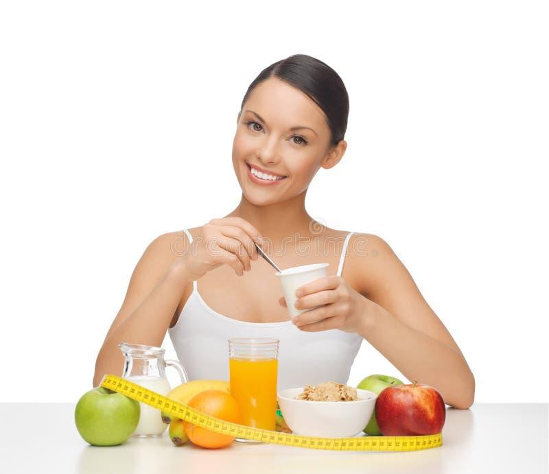 Frau mit gesundem Frühstück und messendem Band stockbild