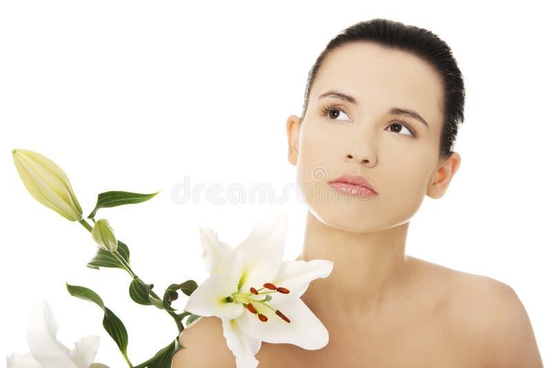 Frau mit gesunder Haut- und Lilienblume stockfoto