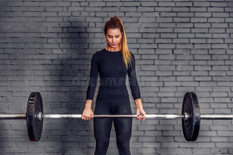Frau mit Gewicht Barbell, der deadlift Übung tut lizenzfreie stockfotos