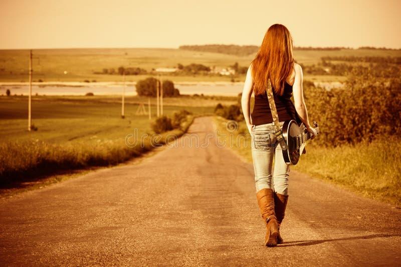 Frau mit Gitarre an der Autobahn stockfotografie