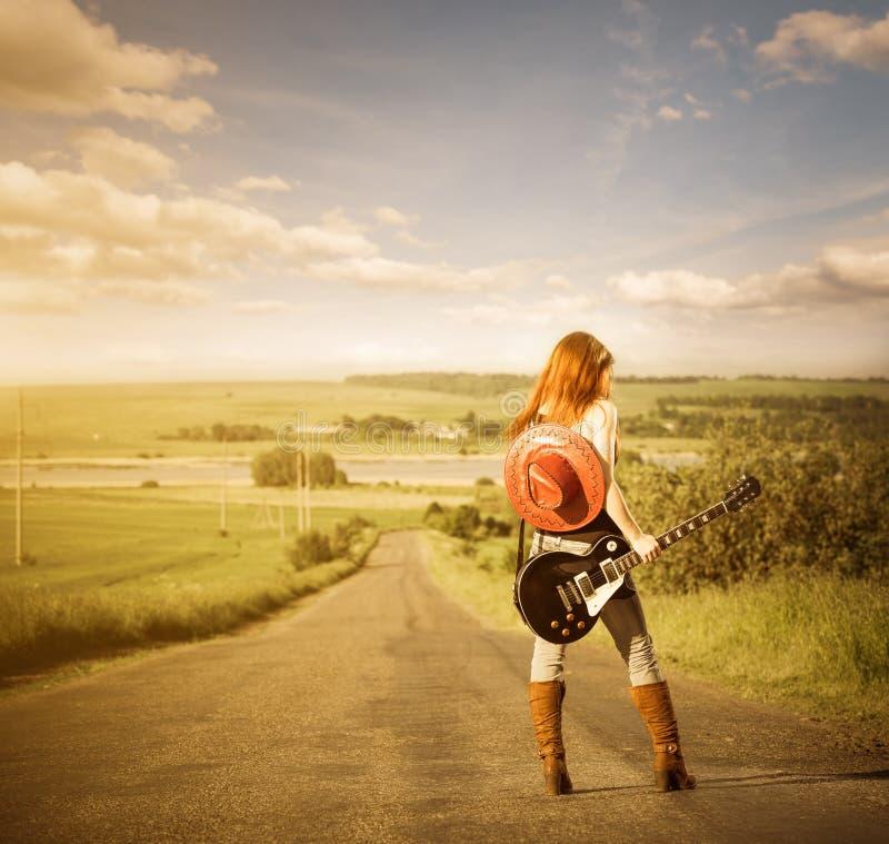Frau mit Gitarre an der Autobahn lizenzfreies stockfoto