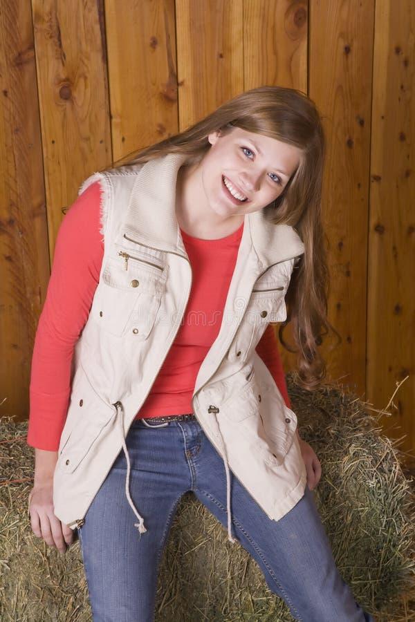Frau mit glücklichem Ausdruck auf Heuballen lizenzfreies stockfoto