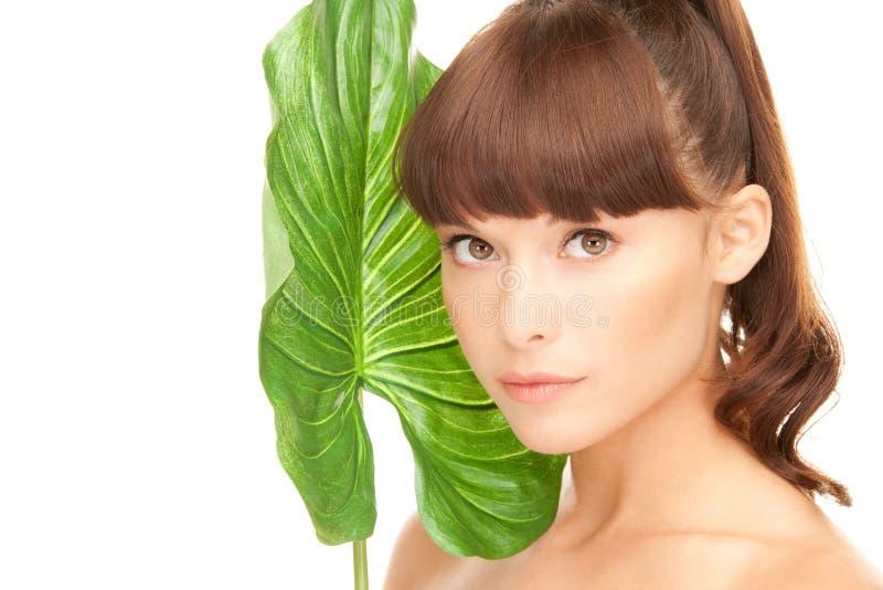 Frau mit grünem Blatt lizenzfreie stockbilder