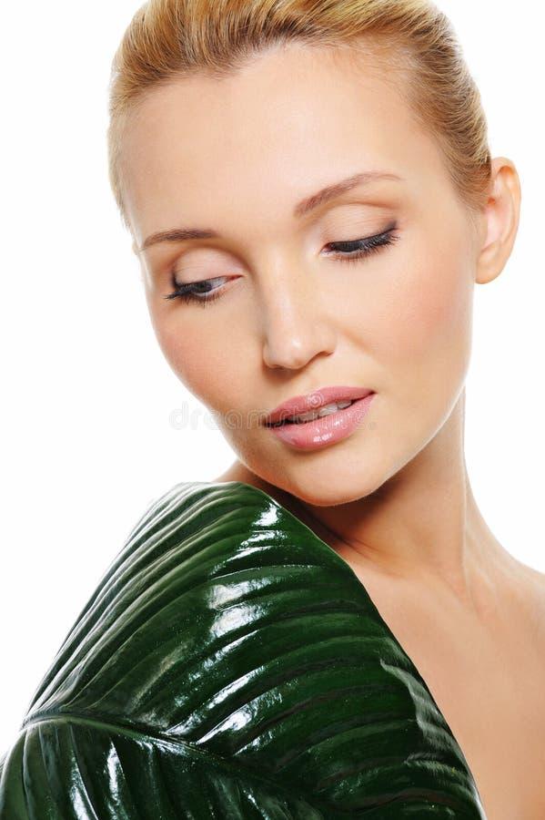 Frau mit grünem Blatt decken ihre Schulter ab stockbild