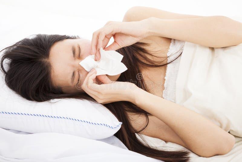 Frau mit Grippe und Legen in Bett stockfotos