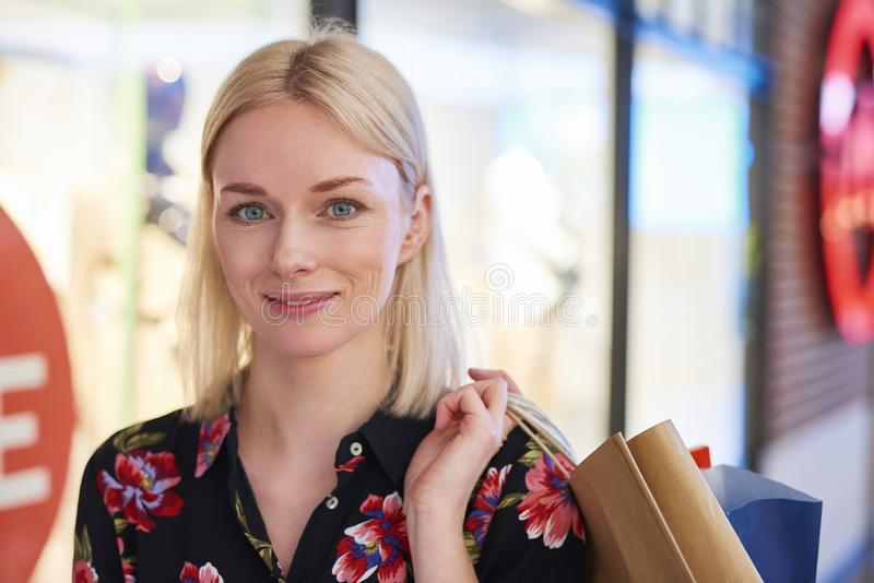 Frau mit großem Lächeln auf ihrem Gesicht nach dem großen Einkaufen lizenzfreie stockfotos