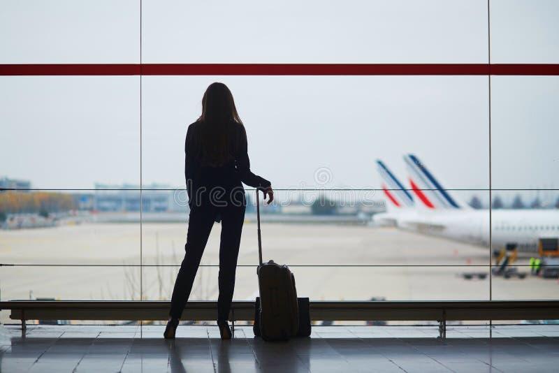 Frau mit Handgepäck im internationalen Flughafen, betrachtend durch das Fenster Flugzeugen stockbilder