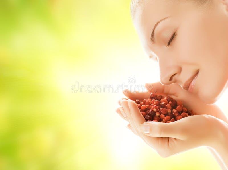 Frau mit Handvoll Erdbeeren lizenzfreie stockbilder