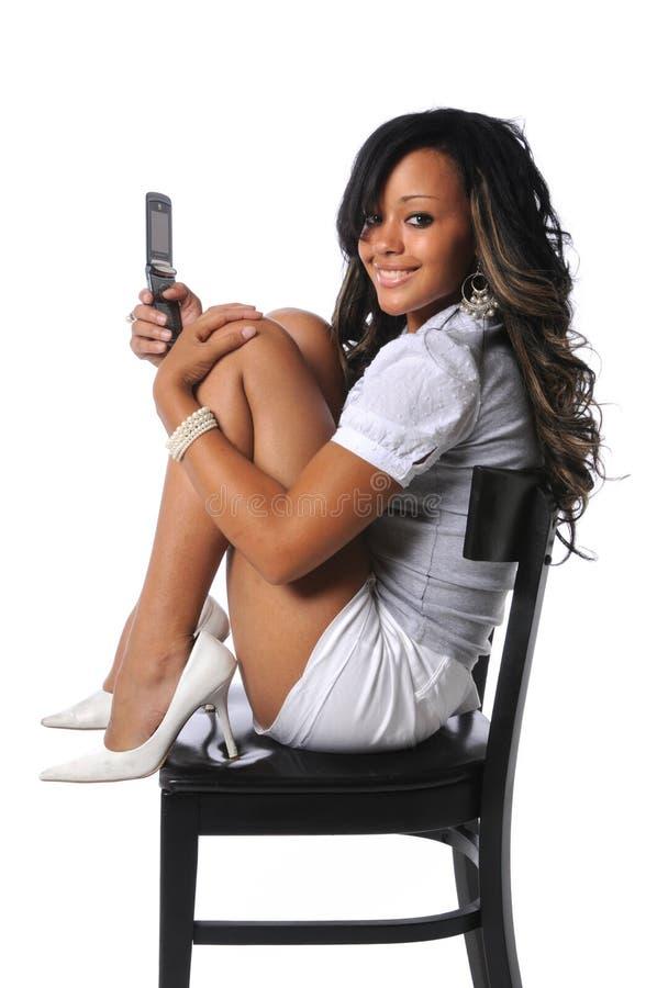 Frau mit Handy auf Stuhl stockfoto