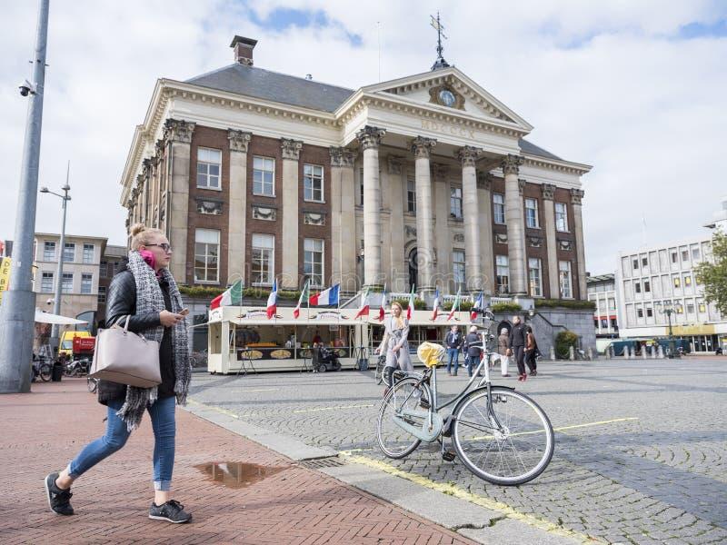 Frau mit Handy führt Rathaus von Groningen in den Niederlanden lizenzfreies stockfoto