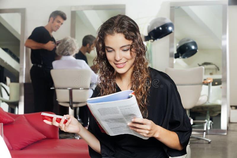 Frau mit Handy-Lesezeitschrift am Haar lizenzfreies stockfoto